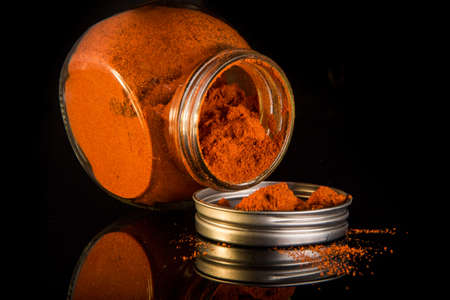 ground red paprika poured from round glass jar on metal cover on black mirror surface with reflection 写真素材 - 133015350