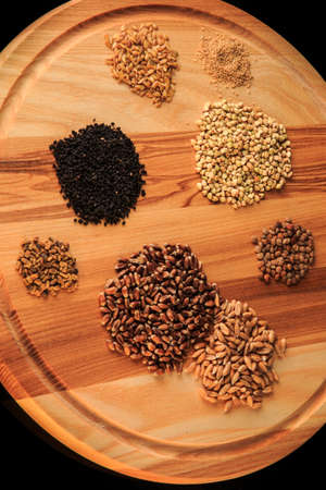 vertical view of wooden board with assorted groat handfuls flax, wheat, buckwheat, black quinoa, millet grains on black 写真素材