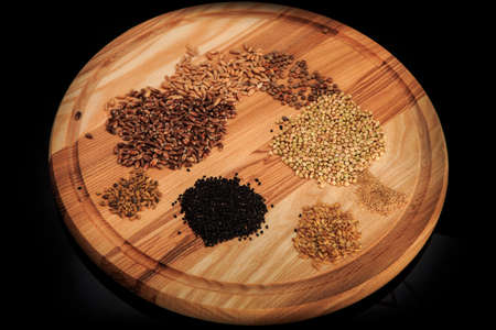 top view closeup wooden board with assorted groat handfuls flax, wheat, buckwheat, black quinoa, millet grains on black 写真素材