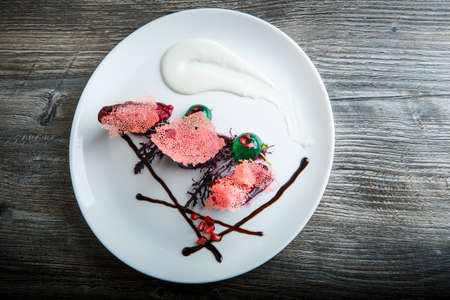 top view on originally decorated delicious restaurant dessert served on white plate on dark wooden table background