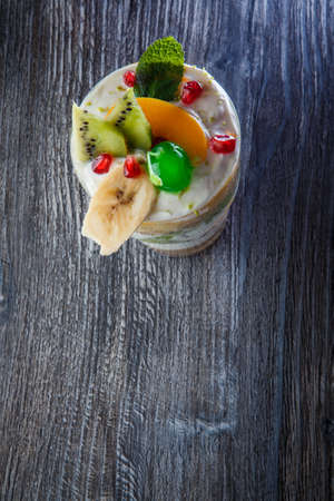 vertical view on delicious fruit and cream dessert with sliced kiwi and green jelly cherry in tall glass on dark wooden table 写真素材 - 133085393