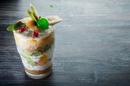 top view on tasty layered fruit and cream dessert with sliced kiwi and green jelly cherry in tall glass on dark wooden table 写真素材 - 133084610