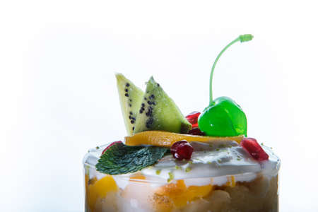 closeup glass with mousse cream and fruits dessert with sliced kiwi and green jelly cherry against white background 写真素材
