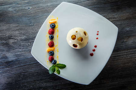 top view on original tasty white and black chocolate ball dessert with assorted berries on white plate on wooden table 写真素材