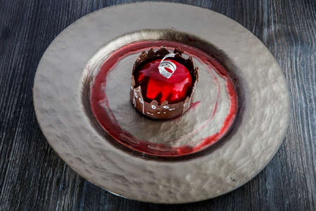 tasty red mirror glazed mousse cake in apple shape with milk chocolate decoration on gold restaurant plate on wooden table