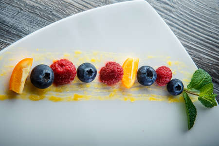 top view closeup row of blueberry, raspberry and sliced orange decorated with mint on white plate on wooden table 写真素材