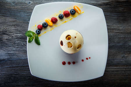 top view on fresh white and black chocolate ball dessert with assorted berries on restaurant plate on wooden table