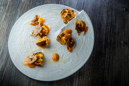 trendy decorated restaurant dessert of crushed cupcakes with sweet sauce and caramelized pumpkin seeds on white plate on wooden table 写真素材 - 133199843