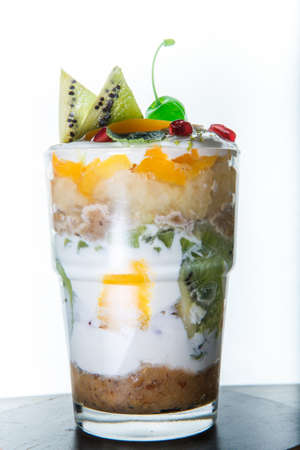 vertical view on original fruits and cream dessert with sliced kiwi and green cherry in tall glass against white background 写真素材 - 133200299