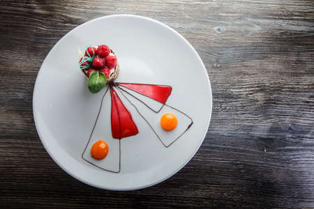 top view on elegantly decorated chocolate raspberry dessert with cream mousse filling on white plate on wooden table 写真素材