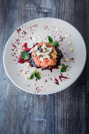 top view on baked apple fine dining decorated with fruit syrop, nuts and mint on restaurant plate on wooden table