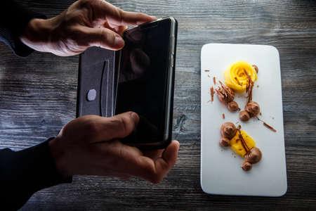 human hands take phone picture of modern restaurant dessert