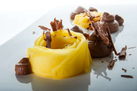 closeup trendy decorated fruit and chocolate mousse dessert against white