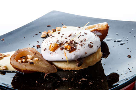 closeup creamy biscuit cake with caramelized pears against white