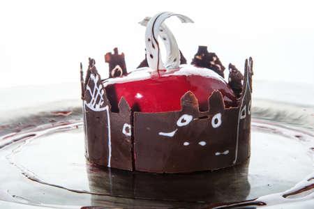 macro view on glazed mousse cake in apple shape against white