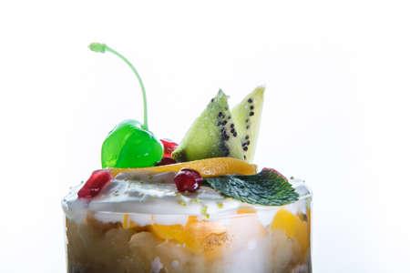 closeup tasty fruit and cream dessert in glass against white 写真素材