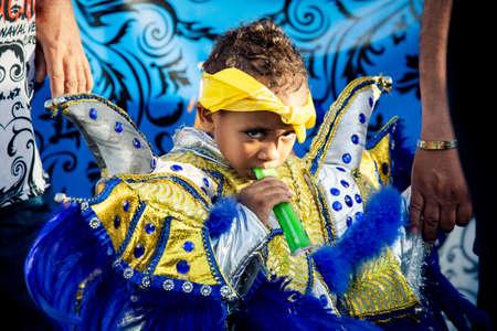 Concepcion De La Vega, DOMINICAN REPUBLIC - FEBRUARY 09, 2020: closeup small boy in pied costume eats ice cream on city street at dominican carnival on February 9 in Concepcion De La Vega