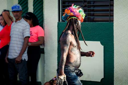 Concepcion De La Vega, DOMINICAN REPUBLIC - FEBRUARY 09, 2020: native man in strange costume walks by city street at dominican annual carnival on February 9 in Concepcion De La Vega