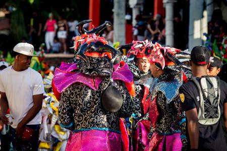 Concepcion De La Vega, DOMINICAN REPUBLIC - FEBRUARY 09, 2020: closeup people in flamboyant costumes pass by city street at dominican carnival on February 9 in Concepcion De La Vega Redakční