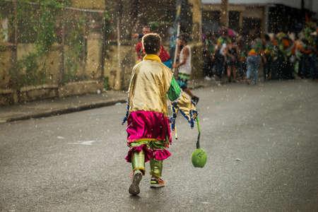 Concepcion De La Vega, DOMINICAN REPUBLIC - FEBRUARY 11, 2019: small boy in colorful carnival costume run away under rain by dominican city street on February 11 in Concepcion De La Vega