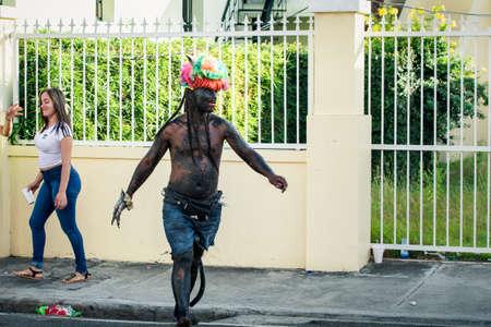 Concepcion De La Vega, DOMINICAN REPUBLIC - FEBRUARY 09, 2020: big man in strange devil costume passes by city street at dominican annual carnival on February 9 in Concepcion De La Vega