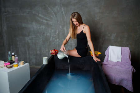 young pretty blond woman pours milk from glass jag into black bath with hot water Stock Photo