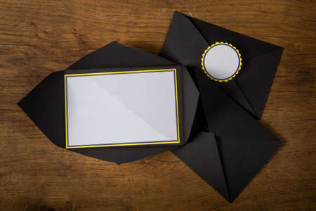 top view closeup on three black envelopes with white invitation space served on dark wooden table surface