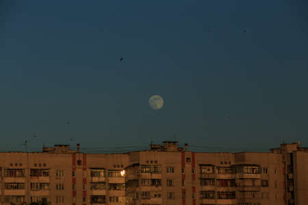 large white full moon on clear blue over an urban high building in evening summertime Stockfoto