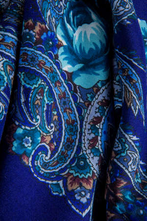 top view closeup on part of bright blue paisley and floral pattern on folded dark blue cotton female shawl