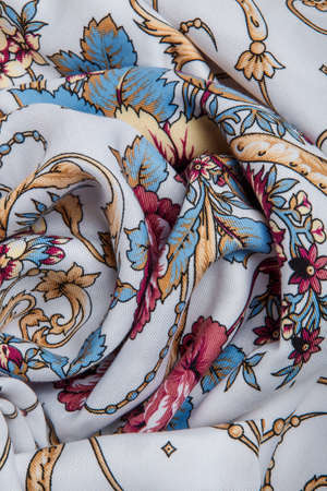 top view closeup on crumpled white cotton female scarf with colorful floral ornament with large red roses and golden lilies 写真素材