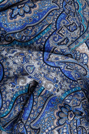 top view closeup on crumpled soft blue cotton scarf with bright oriental ornament with black, white and yellow colors