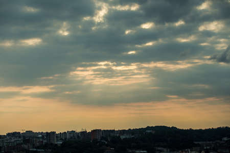 beautiful sunset with fluffy gray clouds on dramatic dark sky above large cityscape silhouettes 写真素材