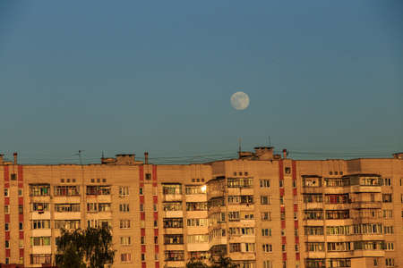 large white full moon on clear blue over an urban city high building in evening summertime