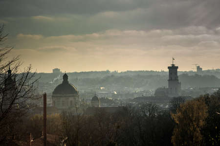 top view from hight castle on city hall, main cathedral, and old houses rooftops in fog in historical district of Lviv city, Ukraine