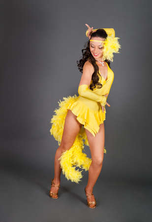 young brunette caucasian woman with curly hair in frank yellow suit dances against gray background in studio