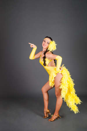 beautiful brunette caucasian model with curly hair in frank yellow suit dances against gray background in studio 写真素材