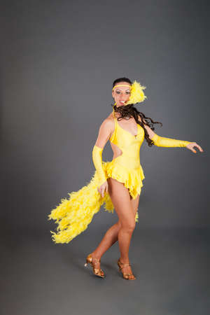 attractive brunette caucasian girl with curly hair in frank yellow suit dances against gray background in studio