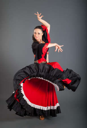 young brunette woman in red and black gypsy style suit and red roses in hair dances against gray background in studio