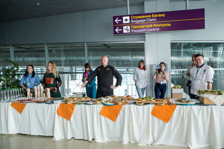 LVIV, UKRAINE - MAY 24, 2018: chefs in different uniforms serving snacks on table for degustation in Lviv airport hall on May 24 in Lviv