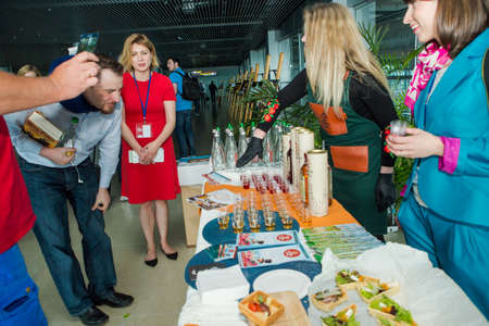 LVIV, UKRAINE - MAY 24, 2018: different passengers try snacks and drinks from free degustation table in Lviv airport hall on May 24 in Lviv 報道画像