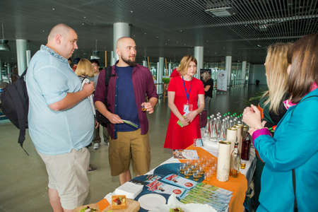 LVIV, UKRAINE - MAY 24, 2018: many passengers try snacks and drinks from free degustation table in Lviv airport hall on May 24 in Lviv