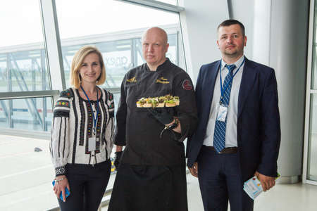 LVIV, UKRAINE - MAY 24, 2018: chef in black uniform hold plate with snacks in Lviv airport hall against arrived airplane on May 24 in Lviv
