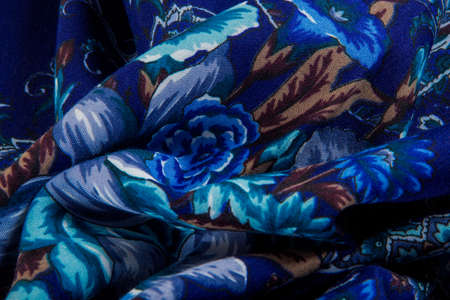 top view macro part of folded textured bright blue paisley and floral rose pattern on dark blue cotton female shawl