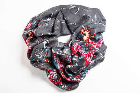 flat lay top view on crumpled gray silk scarf with bright roses floral ornament isolated on white background