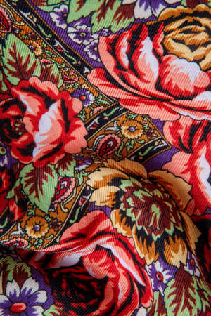 top view closeup on crumpled colorful cotton female scarf with bright floral ornament with large red roses