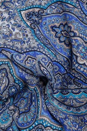 top view closeup on crumpled soft blue cotton scarf with bright oriental paisley ornament with blue, beige and black colors