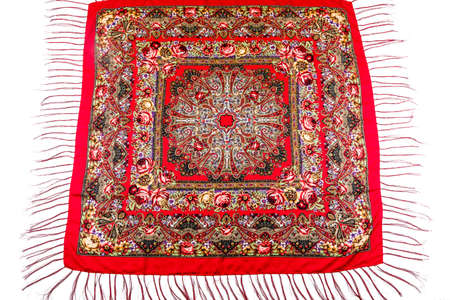 flat lay top view on red cotton scarf with fringe and bright floral roses ornament with red, brown and yellow colors lay on white background