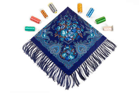 flat lay top view on folded blue cotton scarf with fringe and bright floral ornament with large lilies and oriental paisley on white background