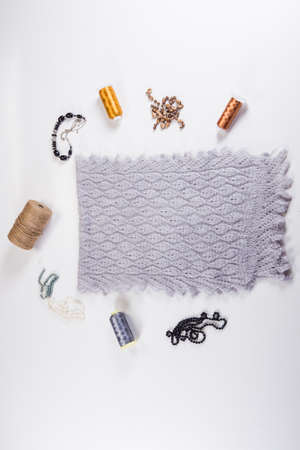 top view on folded handmade gray woolen scarf with knitted pattern designed with different beauty accessories on white background 写真素材