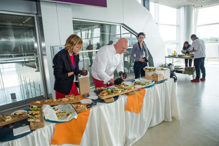 chefs in different uniforms serving snacks on table for degustation in Lviv airport hall